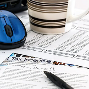 Tax incentive form written in black pen with striped coffee cup and blue mouse