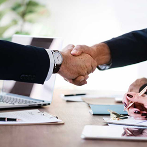 Two business men shaking hands at a desk full of paperwork
