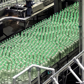 A bunch of green vials on an assembly line