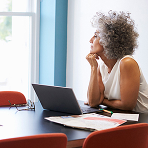 Lady sitting at a table with laptop, papers and glasses looking out a window in deep thoughts