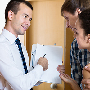 Man holding up and looking over a contract with a husband and wife