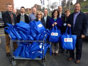 Partner Chris Didio and others posing with blue Red Cross bags