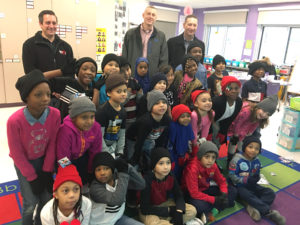 Partners, Sean Daughton and William Michalski and another guy with a group of children with hats for a hat and glove charity event