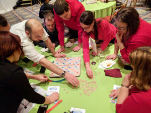A group of Dannible & McKee, LLP employees playing a board game to raise money for charity