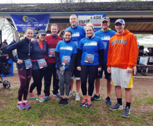 Partners and staff of Dannible & McKee posing for a picture after running in a charity event