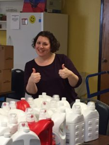 Charla Roth, audit partner of Dannible & McKee, LLP giving thumbs up for an abundance of detergent for a charity