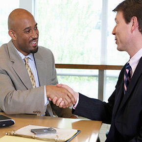 Two business men sitting at a table shaking hands