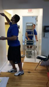 Two Dannible & McKee employees painting the inside of a room and hallway