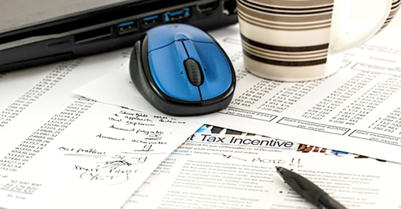 Financial papers on a desk with a blue mouse and stripped coffee mug with pen