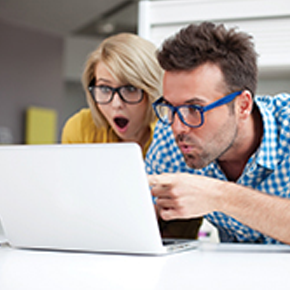 Lady with glasses and man with blue glasses looking happily surprised at something on a laptop