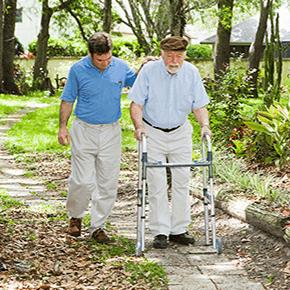 A young man assisting an elderly man with walker walking through garden setting
