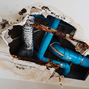 Hole in ceiling with exposed blue pipes