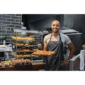 Baker in cafe' holding up full baking sheet
