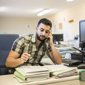 Man working on files and talking on the phone in office