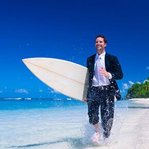 Man in suit with surfboard walking briskly on beach