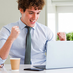 Man excited looking at a computer, with paper cup
