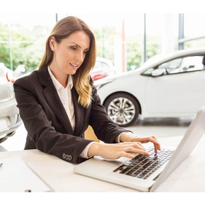 saleswoman on computer with new cars in background