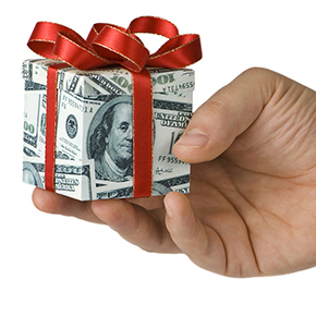 Hand holding gift box wrapped with 100 dollar bill with red bow