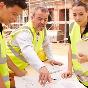 Three construction workers looking at blueprints