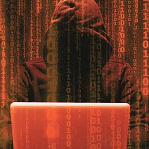 Hacker in hoody on computer