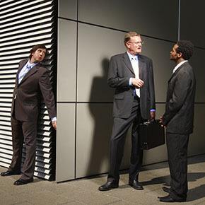 Business man eavesdropping on 2 business men talking
