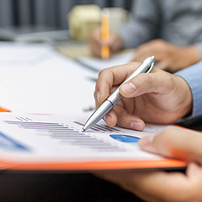 Person pointing at chart on paper with pen