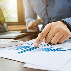Person reviewing financial graph documents