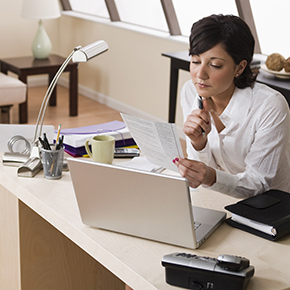 Woman sitting at desk with laptop looking at papers