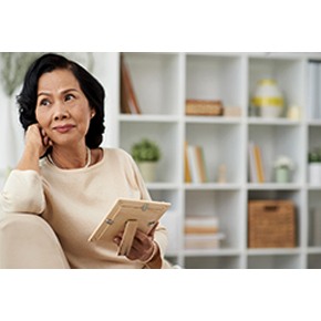 Woman thinking with picture on couch and bookcases in the background