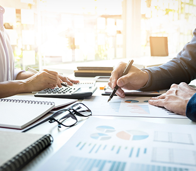 Business man and woman working on financial information the lady is on a calculator and man holding pen with black glasses on desk