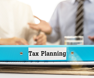 Tax Planning document folder with business team meeting with advisor tax plan services.