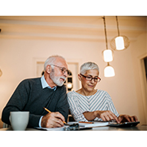 Elderly couple looking at papers and calculator