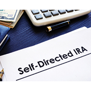 Self-directed IRA written on a white paper and partial view of money and calculator