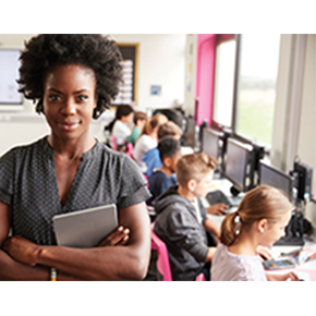 Woman facing front in classroom with students working in background