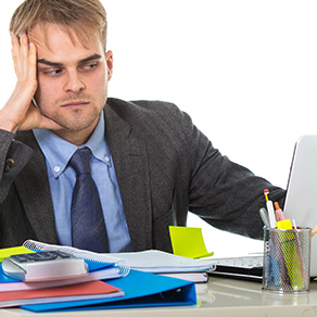 young desperate businessman overworked and upset looking worried and angry sitting at computer desk on white background office in business project stress problem