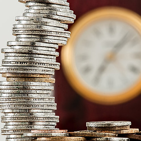 Stack of coins with blurred clock in background