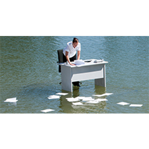 Man standing at a white desk in middle of water with papers scattered on water