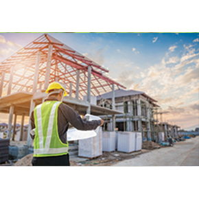 Construction site with a man with a safety hat and safety vest looking at blue prints