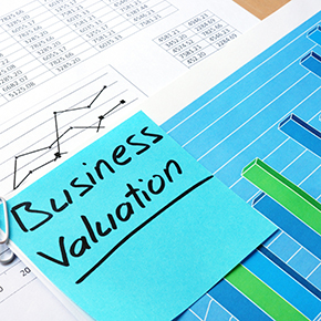 Business Validation blue sticky note on top of papers with charts on them