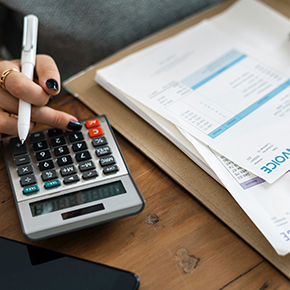 Woman looking at invoice papers while using calculator