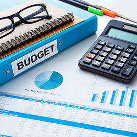 Budget planning reports, Blue budget binder, glasses, calculator and business chart