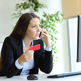 Woman angrily on phone holding credit card and looking at desktop