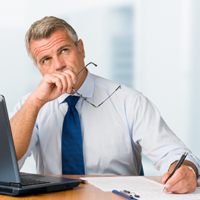 Man thinking while sitting at laptop holding glasses and writing