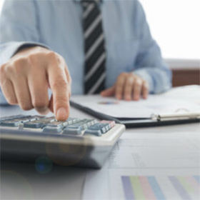 Man sitting at desk with reports, hand working a calculator, charts and stripped tie
