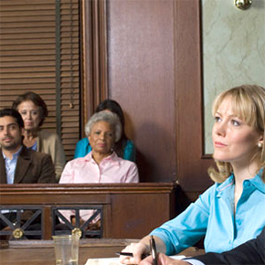 Woman sitting in courtroom with part of jury in background