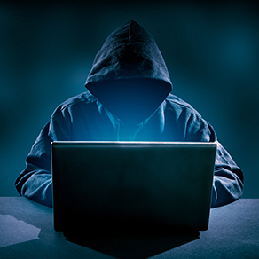 person in hooded jacket sitting in front of laptop hacking into it