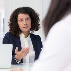 Business woman with black suit and white shirt in concerning discussion with girl