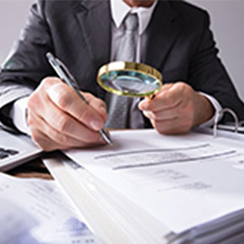 Man using magnifying glass to review papers, has a pen in hand