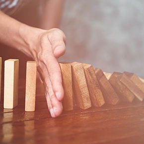 Hand stopping domino effect wooden blocks on wooden table