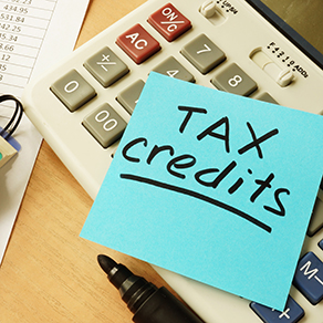 Sticky note on calculator with words tax credits